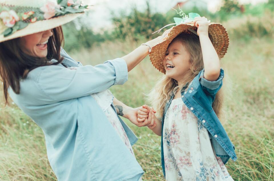 Mutter und Kind lachen mit Sommerhüten